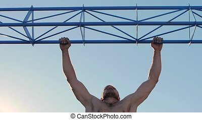 Pulling up on the bar, a man doing push-ups on the horizontal bar. Slow motion