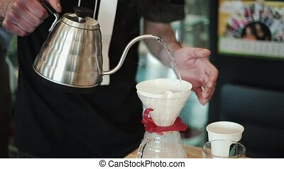 Pump Barista pours boiling water, moistening and washing the filter for pour over kemex