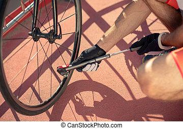 Pump in male hands in sports gloves near wheel
