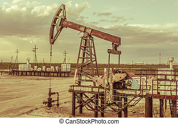 Oil pump jack on a oil field. Cloudy sky background. Extraction of oil. Petroleum concept. Toned.