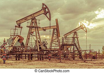 Oil pump jack on a oil field. Sunset sky background. Extraction of oil. Petroleum concept. Toned.