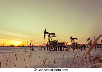 Oil pump jack on a oilfield. Winter sunset sky background. Extraction of oil. Petroleum concept. Toned.