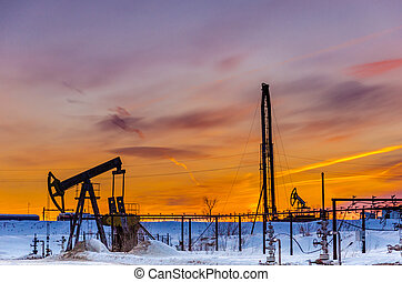 Pump jack, wellhead, pipeline and oil rig during sunset