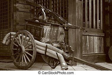 Pump - Sepia shot of an antique firefighting waterpump at a...