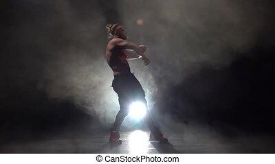Pumped up guy dances a sexy dance . Black smoke background....