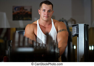 Pumped young man with tattoo in gym