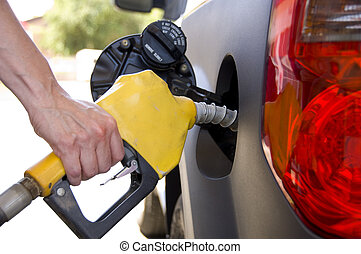 Pumping Gas or Petrol - A hand holding a gasoline nozzel...