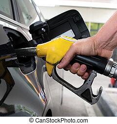 gasoline - pumping gasoline on a black car in station