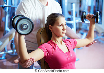 Pumping muscles - Portrait of pretty girl training in gym...