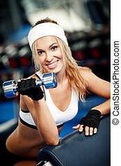 Pumping up biceps - Smiling athletic woman pumping up biceps...