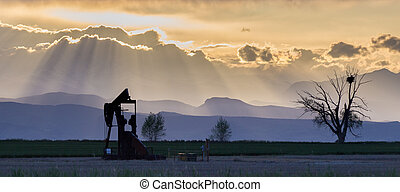 Pumpjack and tree with nest with Rocky Mountains and crepuscular rays