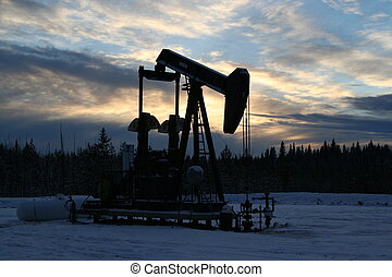 Pumpjack backlit by setting sun