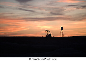 industry sunset - pumpjack and water tower shot silhouetted on a hill in rural Wyoming