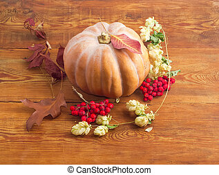 Pumpkin among rowan and autumn leaves on a wooden surface