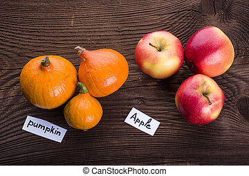 Pumpkin and apples on wooden background