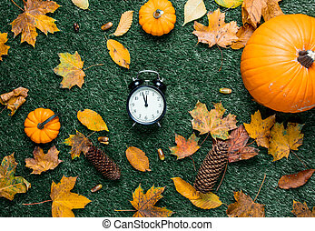 Pumpkin and autumn season leaves with alarm clock