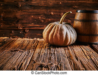 Pumpkin and barrel on old wooden table