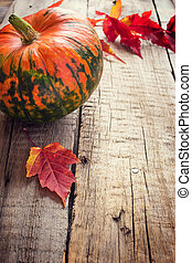 Pumpkin and purple leaves  on an old wooden background