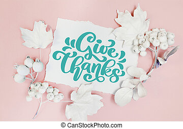 Pumpkin, berries and leaves with white frame mockup on a pink pastel autumn background. Greeting card for Thanksgiving Day in rustic style with Give Thanks text. Flat lay. Top view