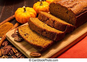 Pumpkin Bread - Sliced pumpkin bread loaf sitting on wooden...