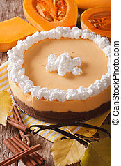 pumpkin cheesecake with cinnamon, vanilla and whipped cream close-up. Vertical