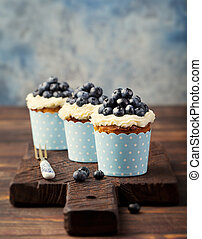 Pumpkin cupcakes decorated with cream cheese frosting and fresh blueberries Copy space