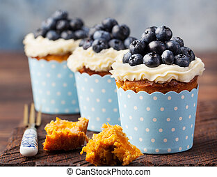 Pumpkin cupcakes decorated with cream cheese frosting and fresh blueberries on a wooden background