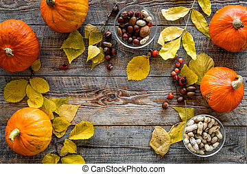 Pumpkin harvest. Pumpkins near nuts and autumn leaves on wooden background top view copyspace