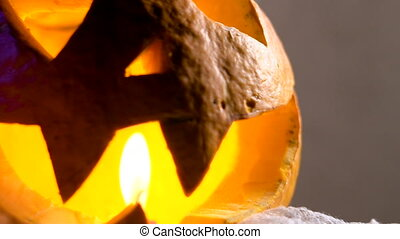pumpkin head lit from within, her eyes, nose and mouth flickering candle light.