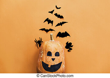 Pumpkin jack lantern and black bats, ghost, spider paper decorations on yellow background, copy space. Halloween flat lay. Trick or treat concept. Happy Halloween