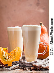 Pumpkin latte with whipped cream and spices on wooden ...