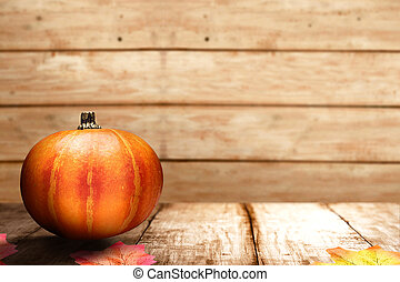 Pumpkin on wooden table with autumn leaves