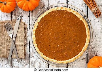 Pumpkin pie, downward view on rustic white wood background