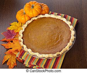 pumpkin pie on table next to pumpkins
