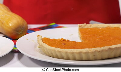 Pumpkin pie slice decorated with powdered sugar on a plate -...