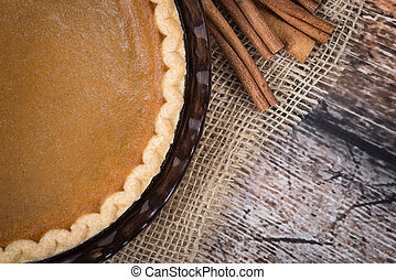 Pumpkin pie with cinnamon sticks on wooden vintage table