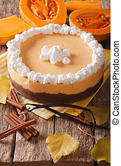 pumpkin pie with cinnamon, vanilla and whipped cream close-up. vertical