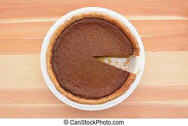 Pumpkin pie with one slice taken