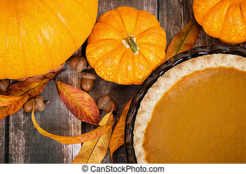 Pumpkin pie with pumpkins and autumn decorations on rustic table