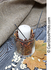 Pumpkin seeds and candle. Nearby are dried maple leaves. On brushed pine boards painted black and white.