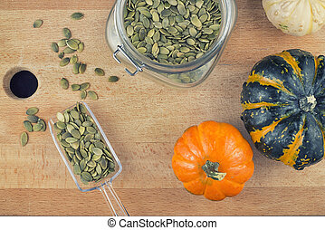 Pumpkin seeds and squash over wood