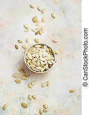 Pumpkin seeds in bowl isolated on white background