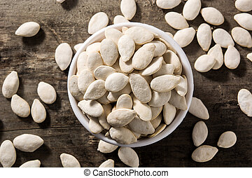 Pumpkin seeds in white bowl on wooden background.