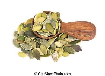 Pumpkin seeds in wooden spoon, isolated on white background. Green pepita seeds.