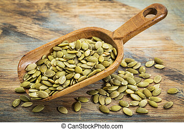 pumpkin seeds on a rustic wooden scoop against grunge painted wood background