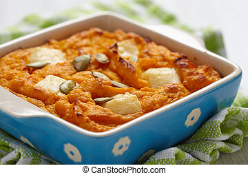 Pumpkin souffle with cheese and seeds on white table