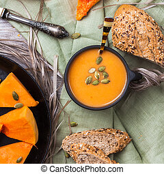 Pumpkin soup in a mug on rustic table