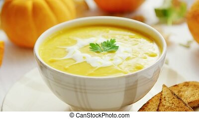 Pumpkin soup in bowl served with bread - Yellow creamy ...
