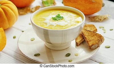Pumpkin soup in bowl served with bread - Yellow creamy...
