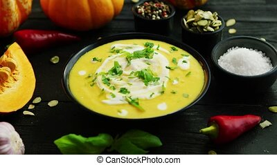 Pumpkin soup in bowl sprinkled with herbs - From above view...